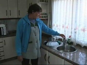 Una vecina de Faramontaos muestra el agua sucia que sale del grifo