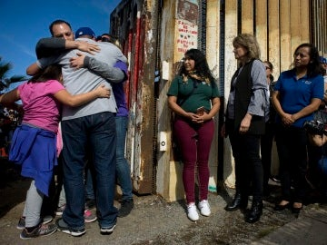 Un grupo de personas abrazan a sus familiares en una de las puertas de la valla fronteriza entre Estados Unidos y México