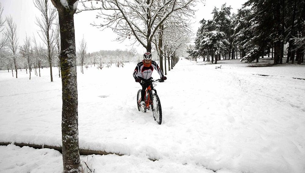 Un ciclista se aventura en el parque de Olarizu de Vitoria, ciudad que ha amanecido cubierta por la nieve
