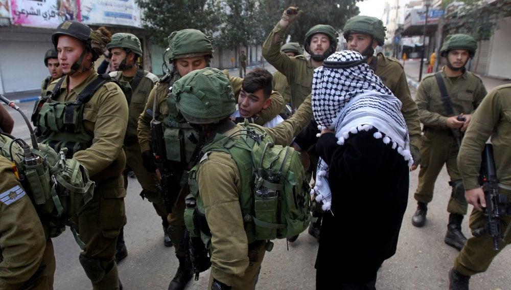 Soldados israelíes detienen a un palestino durante los enfrentamientos en la ciudad cisjordana de Hebrón, Palestina
