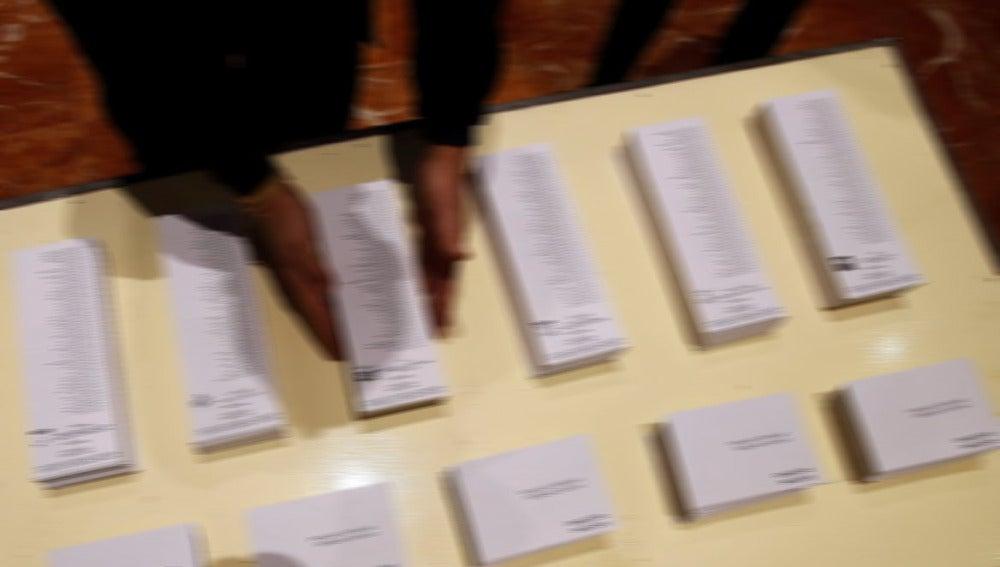 Una persona ordenando papeletas electorales