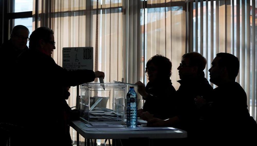 Una persona vota en una mesa electoral en el Casal Mossèn Guiteras en la ciudad de Vic