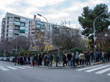 Personas esperando el momento de votar frente al colegio Narcís Monturió de Barcelona