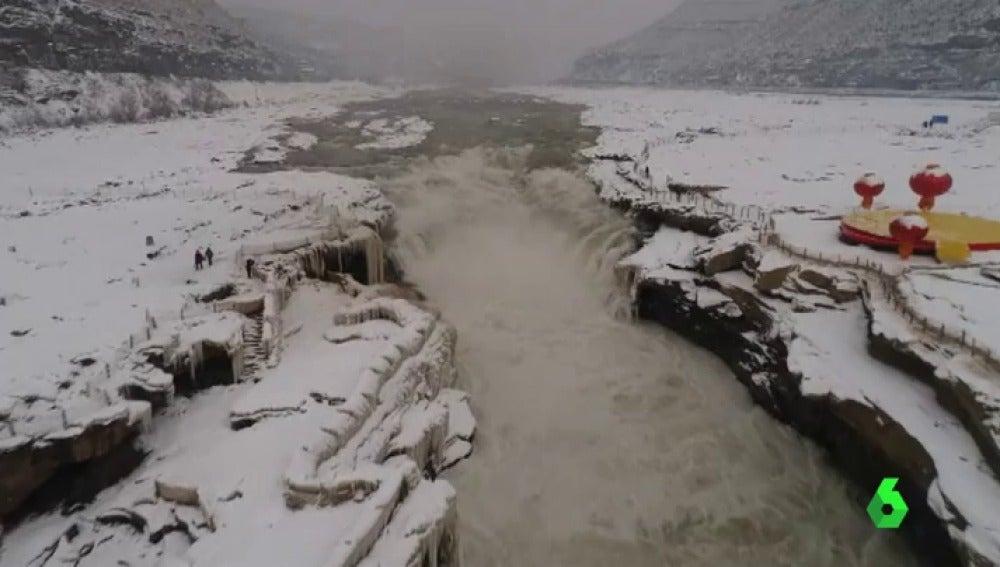 El frío y la nieve congelan y tiñen de blanco parte de la cascada Hukou