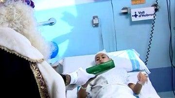 Un rey mago entrega un regalo a un niño en el hospital