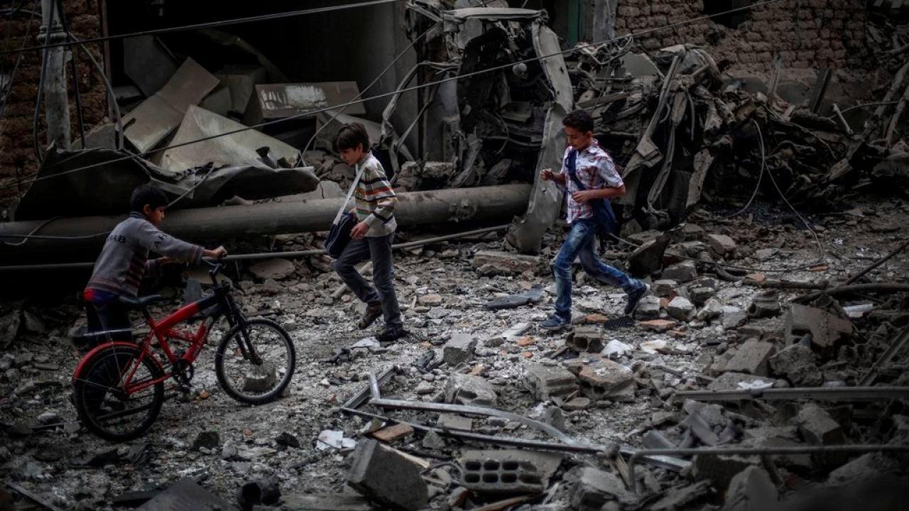 Niños sirios observan los daños ocasionados tras un bombardeo a las afueras de Damasco