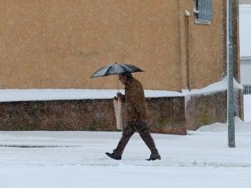 Un hombre camina bajo la nieve en la localidad salmantina de Guijuelo