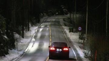 Los coches circulan por la carretera bajo la luz de las farolas inteligentes