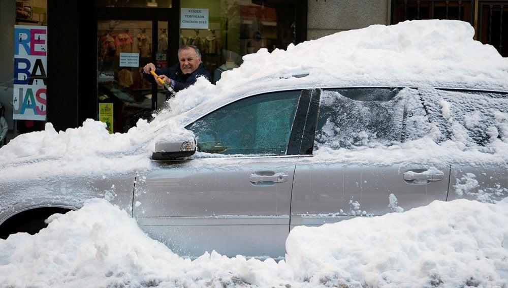 Un hombre retira la capa de nieve de un coche