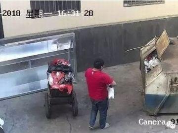 Una captura del momento en el que el padre arroja a su hija al contenedor