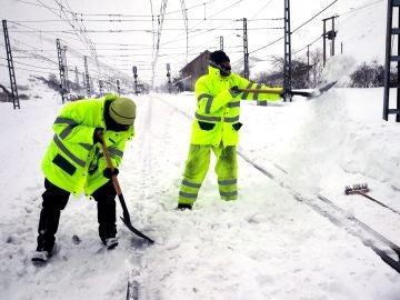 Dos operarios retiran la nieve en la estación de ferrocarril de Busdongo