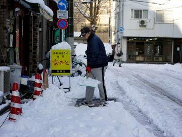 Un hombre despeja la nieve de una acera después de una nevada en Tokio