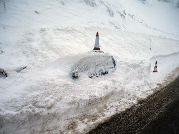 Un vehículo permanece cubierto de nieve en el pueblo de Pajares (N-630)
