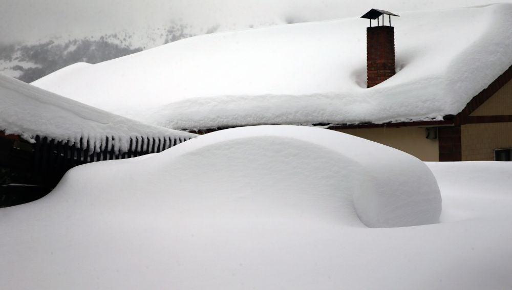 Un vehículo cubierto de nieve, en el pueblo asturiano de Pajares
