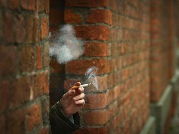 Una mujer fuma en la ventana de su casa