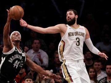 Mirotic intenta coger el balón ante Cunningham