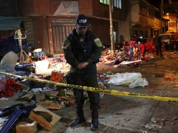 Una unidad de bomberos y miembros de la policía inspeccionan el lugar donde se produjo una explosión