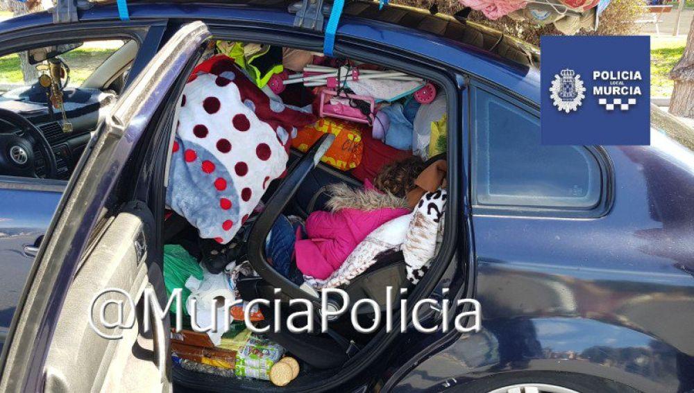 Una niña atrapada entre los enseres de un coche