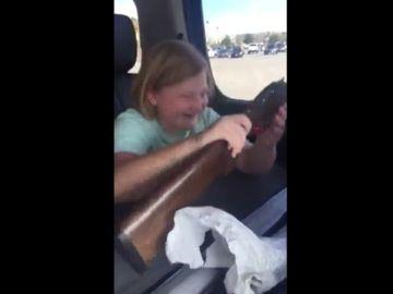 La niña en el momento de recibir el arma