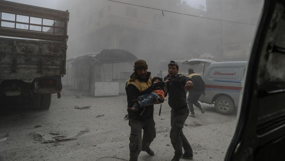 Un voluntario de los Cascos Blancos lleva a un niño herido en brazos en Guta