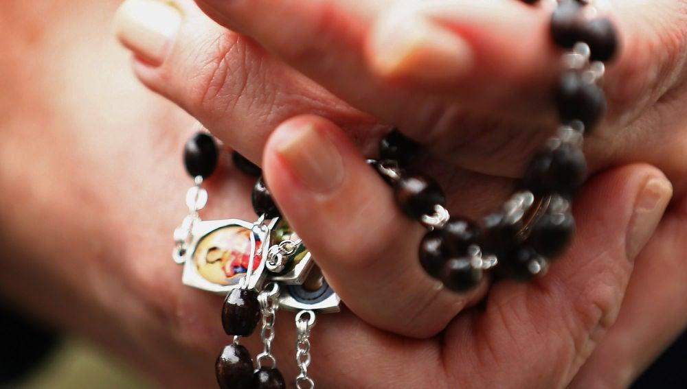 Una mujer con un rosario en las manos