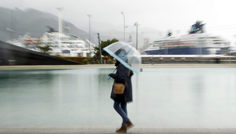 Una mujer paseando bajo la lluvia