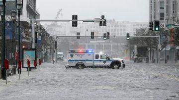 Un coche de policía corta el tráfico de la inundada Seaport Boulevard, durante una tormenta en el distrito Seaport de Boston, Massachusetts