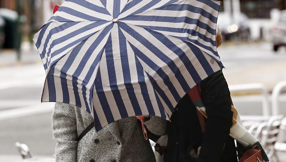 Dos mujeres se protegen con un paragüas de la lluvia y el viento hoy en Pamplona
