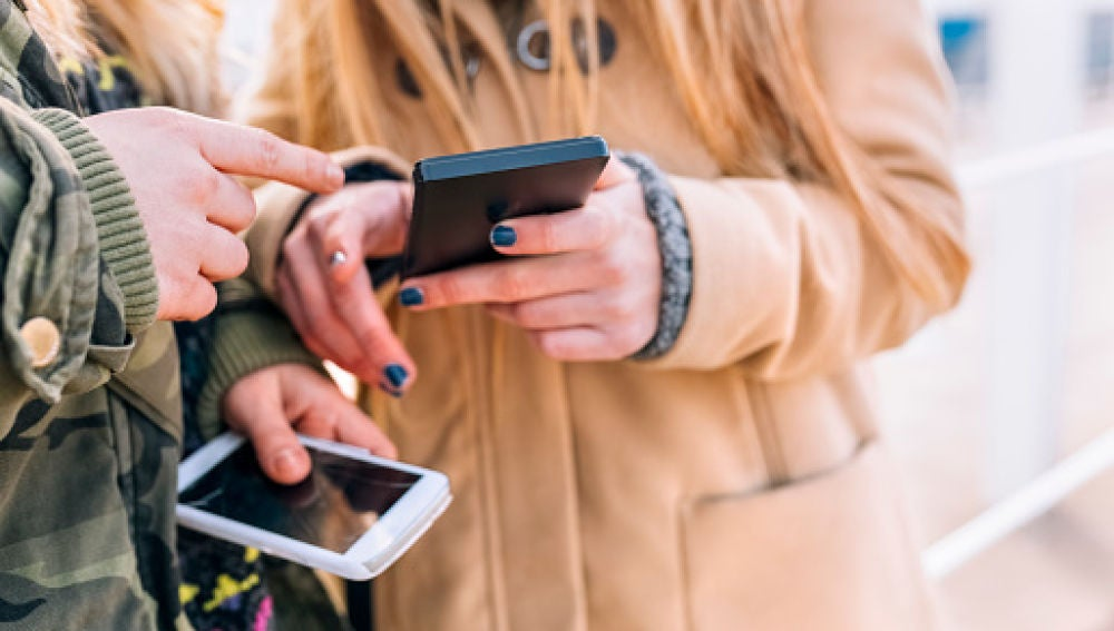 Imagen de archivo de dos jóvenes mirando sus móviles