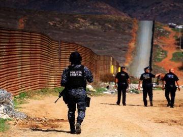 Policías federales custodian la barda fronteriza que delimita a México con territorio norteamericano
