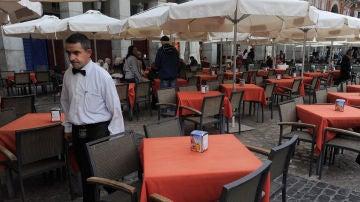 Camarero sirviendo en una terraza.