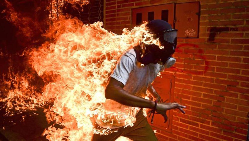 El manifestante José Víctor Salazar Balza en llamas durante los enfrentamientos con la policía antidisturbios