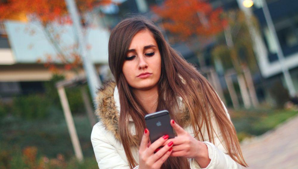 Una adolescente mira el móvil