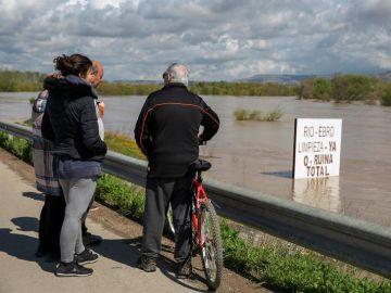 Unos vecinos contemplan el río Ebro, que se ha desbordado a sus paso por Novillas