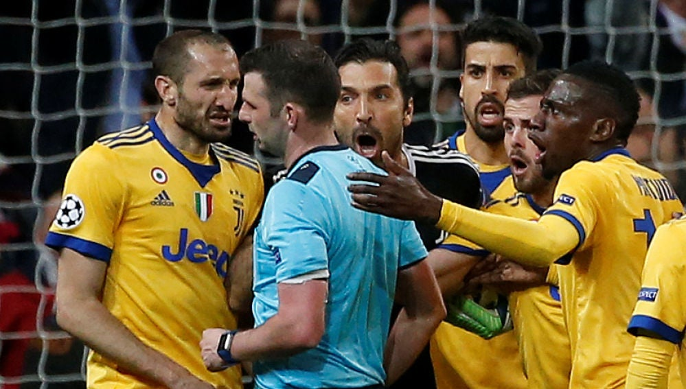 El colegiado Michael Oliver, acosado por los jugadores de la Juventus