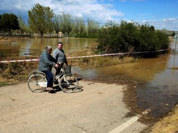 Vecinos de la localidad zaragozana de Monzalbarba contemplan su vivienda, aislada por la crecida del río Ebro