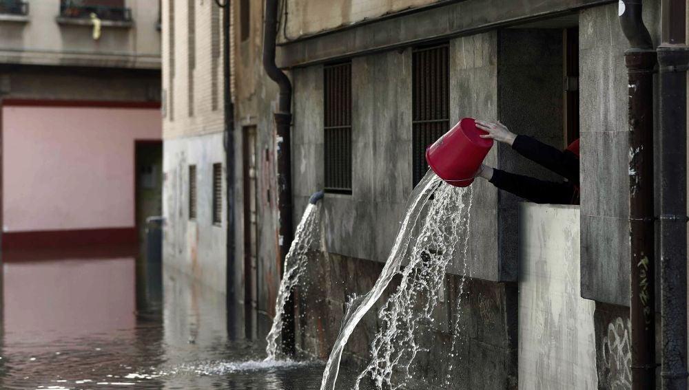 Una persona vierte el agua recogida que ha entrado en las cocinas de un restaurante de Tudela