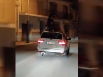 Varias personas bailando sobre un coche en circulación