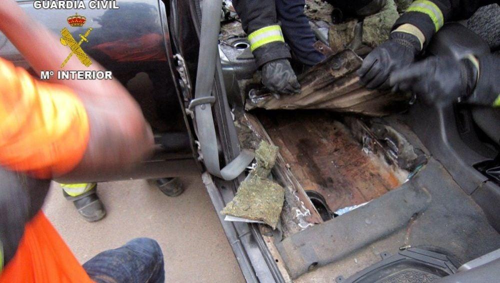 La policía abriendo un doble fondo de un coche para sacar a un menor
