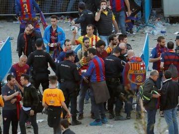 Agentes de la Policía Nacional junto a seguidores del Barcelona en los exteriores del Wanda Metropolitano