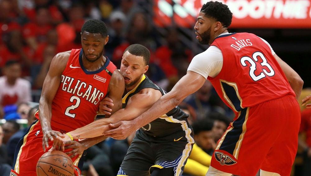 Curry intenta robar el balón entre Holiday y Davis