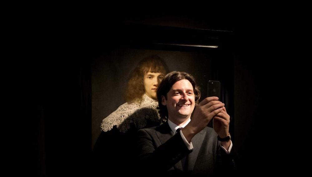 """El historiador y marchante de arte holandés Jan Six se toma un selfi delante de la obra """"Retrato de un joven caballero"""" de Rembrandt"""