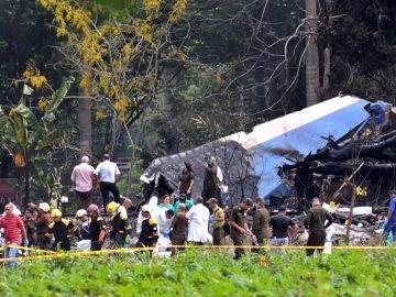 olicías y militares trabajan entre los restos del avión Boeing-737