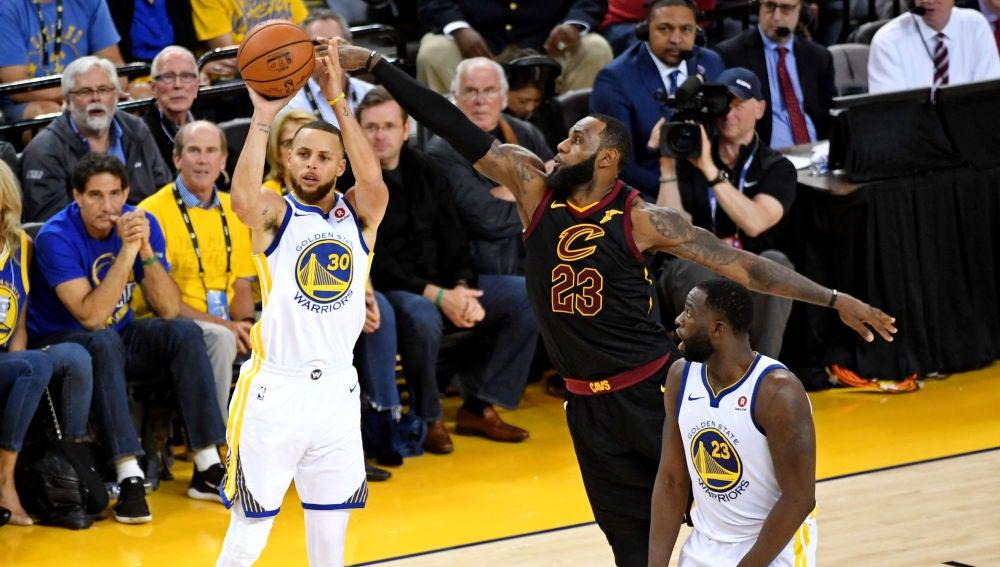 Curry lanza un triple ante la defensa de LeBron James