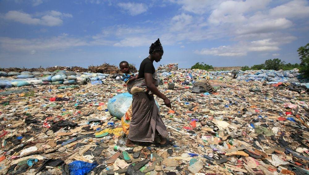 Imagen de archivo de una mujer que rebusca botellas de plástico en el basurero de Akouedo, en Abiyán, en Costa del Marfil