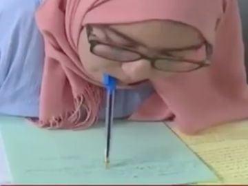 Una joven con parálisis en brazos y piernas escribe un examen con el bolígrafo en la boca