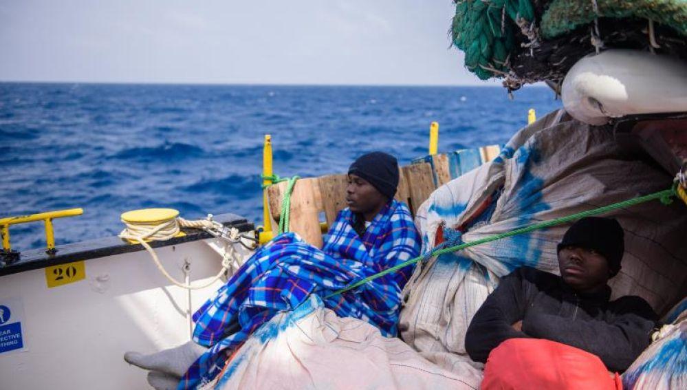 Inmigrantes descansan a bordo de un barco después de ser rescatados en el Mediterráneo