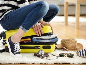 Mujer cerrando maleta