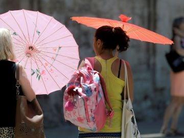 Dos mujeres se protegen del calor con unas sombrillas