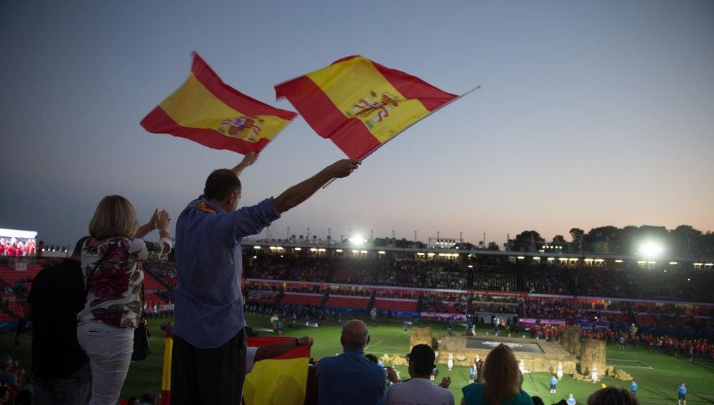 Dos personas agitan banderas al paso de los atletas españoles durante la inauguración de los XVIII Juegos Mediterráneos